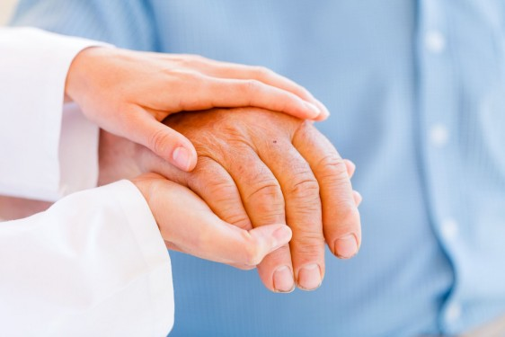 mujer sostiene la mano de adulta mayor