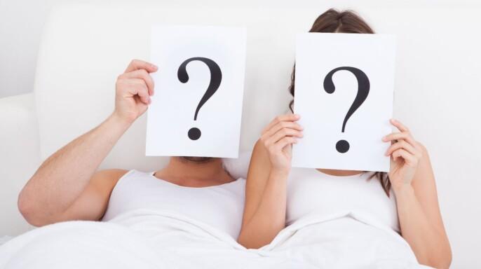 pareja en una cama mostrando signos de interrogación