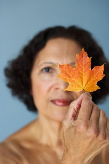 Mujer de más de cincuenta años con una hoja de otoño