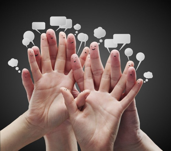 Manos con dedos ilustados con sorostros sonrientes y burbujas de dialogos
