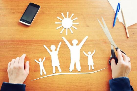Recorte de papel de familia en una mesa de madera persona sosteniendo tijeras