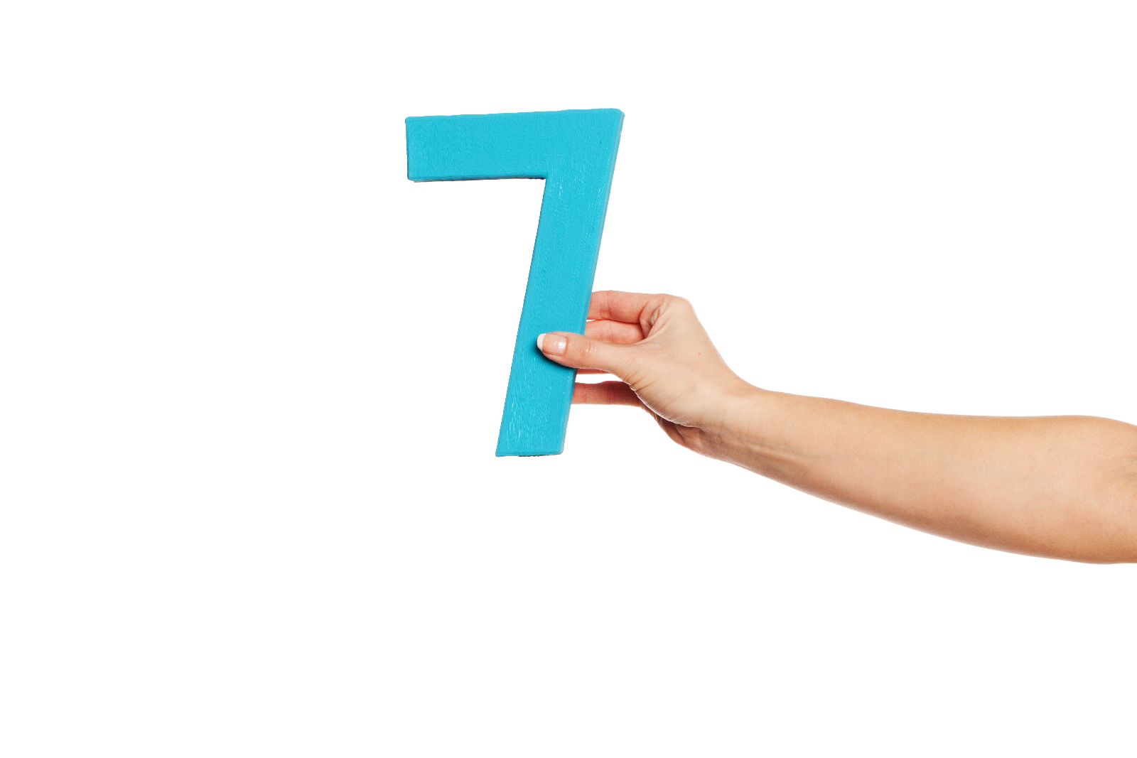 Mano de una mujer que sostiene un número siete azul en un fondo blanco