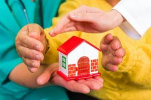 manos de familia protegiendo casa de juguete