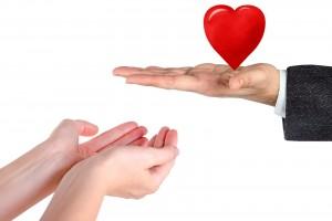 persona sostiene figura en forma corazón y otra extendiendo sus manos para recibirlo