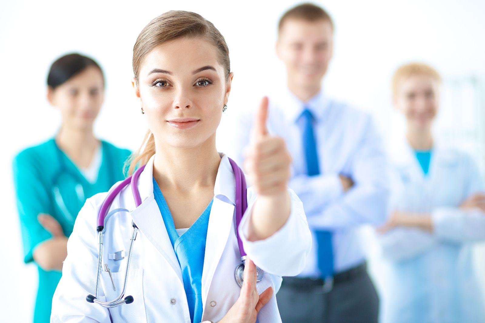 Doctora con pulgar hacia arriba, al fondo colaboradores observando