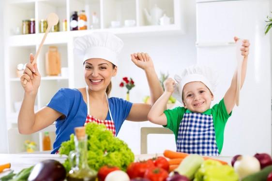 Madre e hijos sonriendo y cocinando con verduras