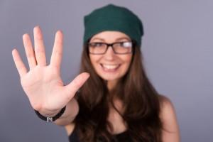 Mujer sondiendo haciendo un gesto de cinco con la mano en alto