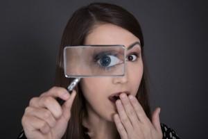 mujer sosteniendo lupa en su rostro