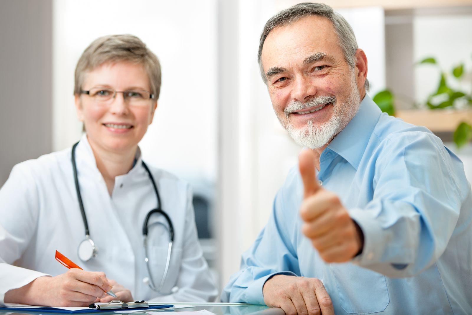 Adulto mayor con pulgar hacia arriba con doctora en el fondo