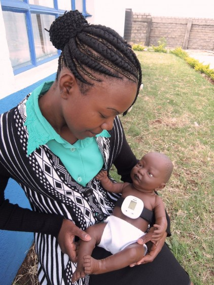 Niña sosteniendo muñeco con un Monitor de Respiración Infantil
