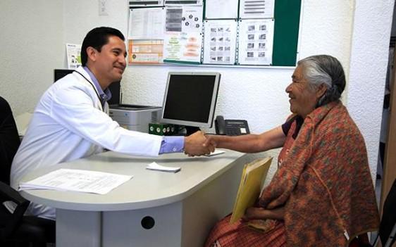 Médico saluda de mano a adulta mayor indígena