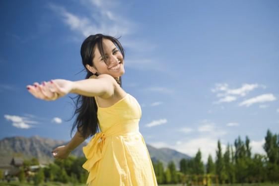 Mujer en vestido amarillo con los brazos abiertos al fondo un bosque