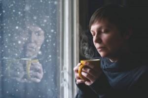 Mujer con una taza en la mano viendo nevar