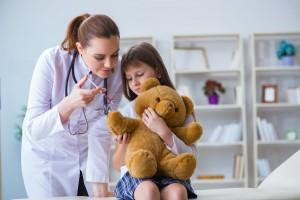 Doctora examinando a niña con un oso de peluche
