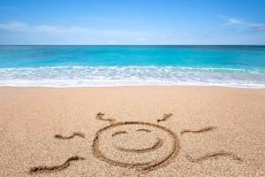 Panorámica de una playa con un dibujo de sol sonriente en la arena