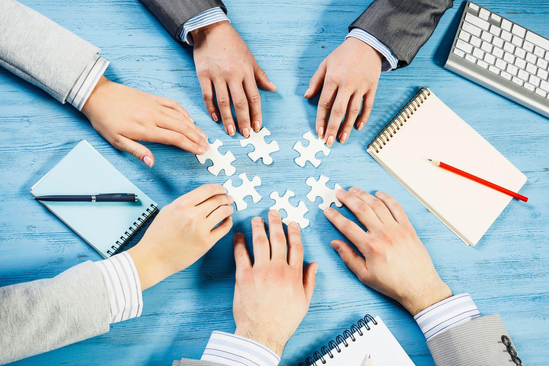 manos de diversas personas uniendo piezas de rompecabezas
