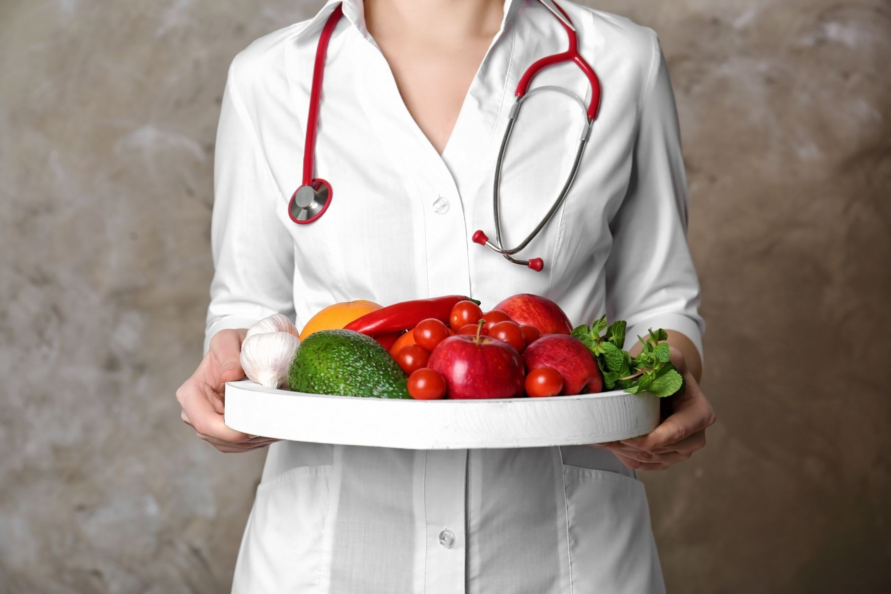 médica sosteniendo alimentos saludables