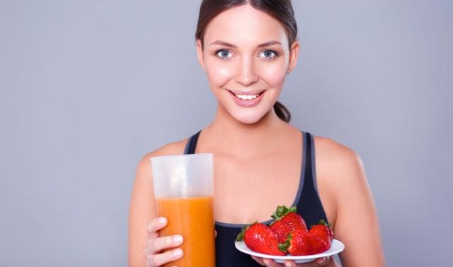 mujer joven sonriendo, sostiene con sus manos un vaso con jugo y un plato con fresas