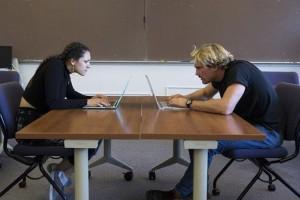 Dos estudiantes de la Universidad Estatal de San Francisco muestran la postura en la que las personas se comprimen el cuello en la computadora.