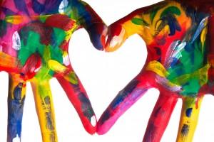 Manos pintadas con muchos coloers en forma de corazón