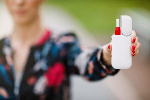 Close-up Of Woman Holding Electronic Cigarette In Hand.  Beautiful girl uses an electronic cigarette. Tobacco system IQOS.