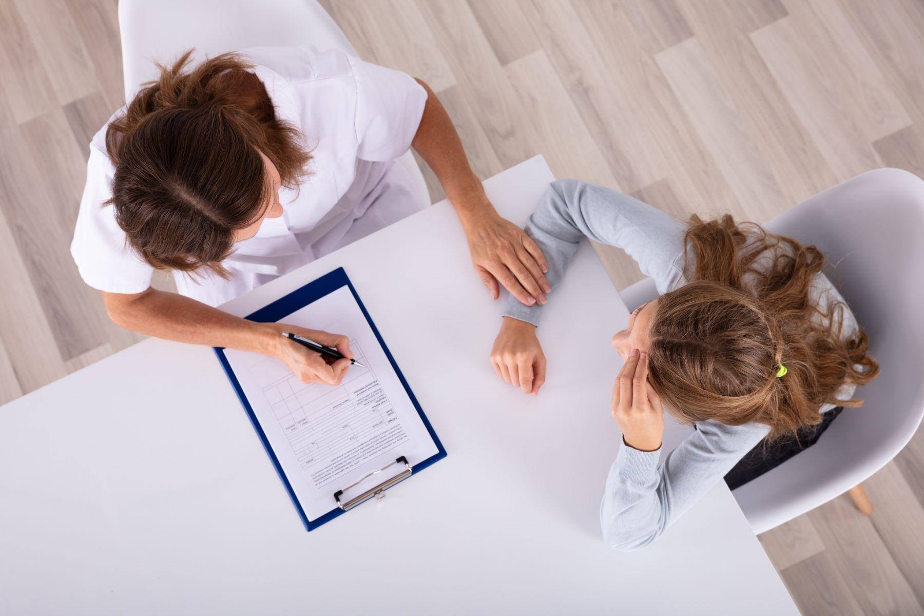 Doctora con portapapeles mirando deprimido chica paciente en clínica