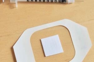 El nuevo parche se muestra debajo de una vacuna tradicional contra la gripe basada en agujas