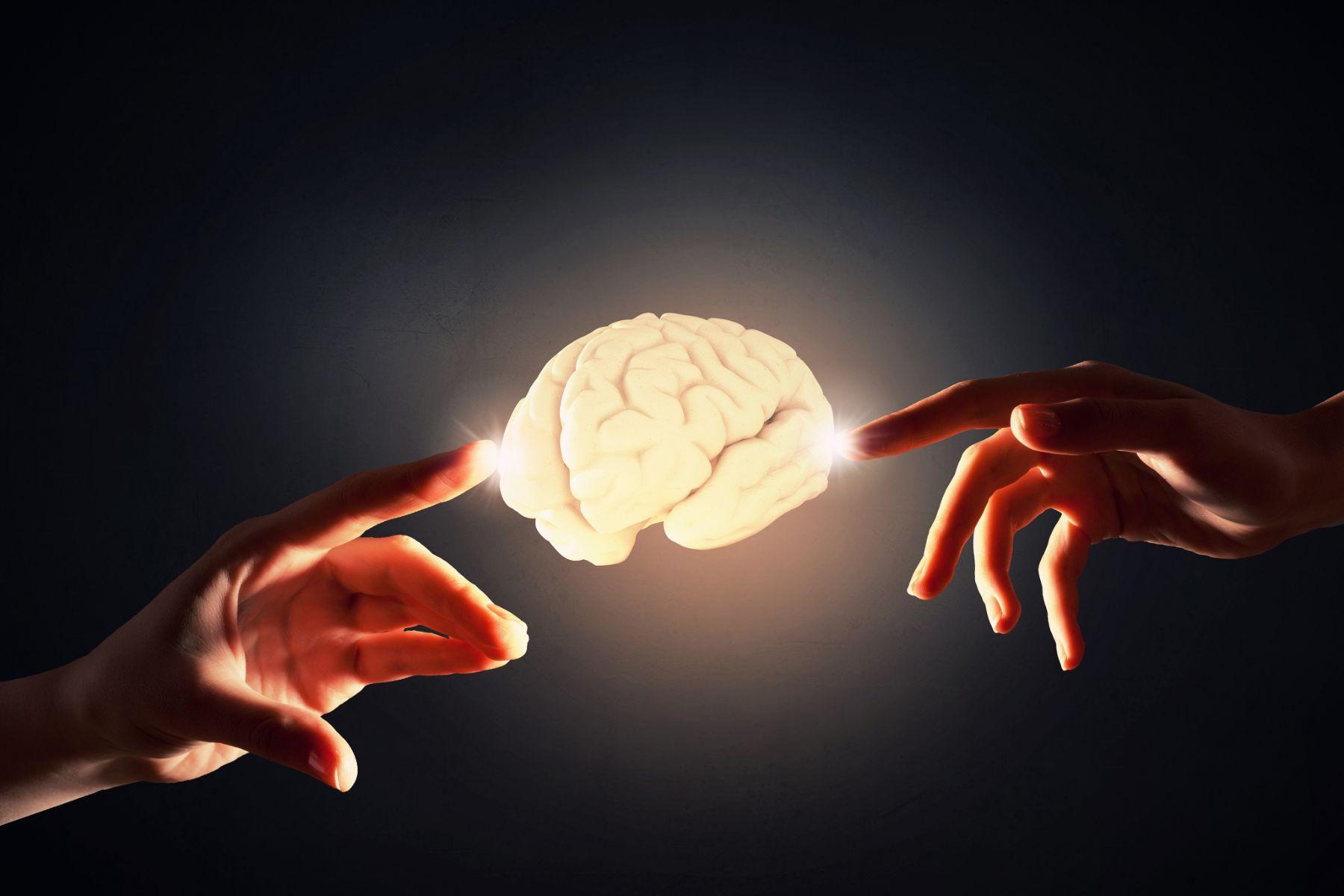 manos tocando un cerebro iluminado