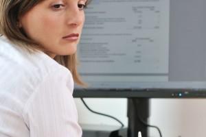 Mujer enfrente de una computadora aplicandose gotas