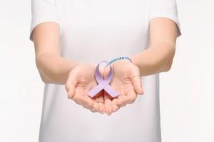 mujer con manos extendidas sostiene listón lila
