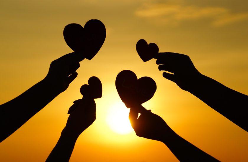 Manos sosteniendo corazones contra la puesta de sol