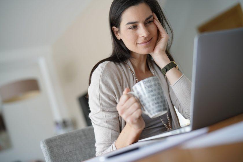 mujer tomando tasa de cafe y trabajando