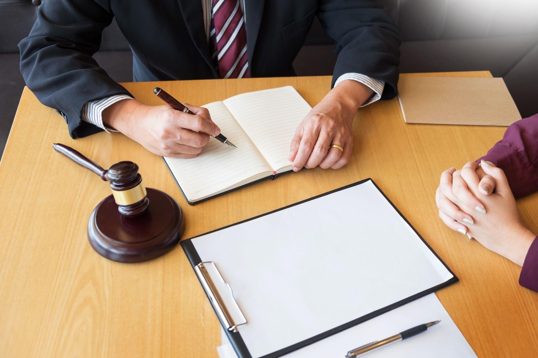 Dos personas firmando documentos y un mazo