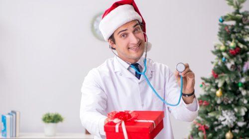 Médico con caja de regalo en el hospital