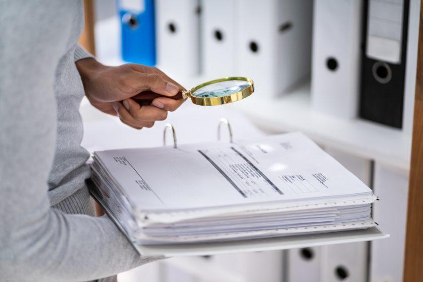 Acercamiento de un auditor revisando documentos con lupa