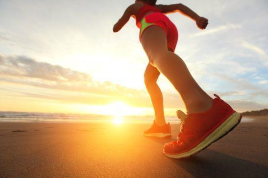 mujer corriendo hacia la puesta de sol