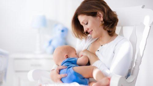 Joven madre feliz con bebé en casa