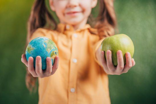 Niña que sostiene el modelo globo y manzana sobre fondo borroso, concepto de día de la tierra