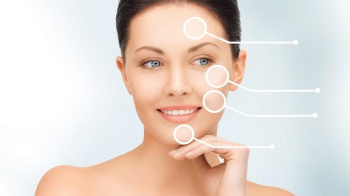 Acercamiento a rostro de mujer con iconos en puntos en la piel