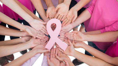 Mujeres vestidas de rosa y alrdedor de un moño rosa unienso tocandolo