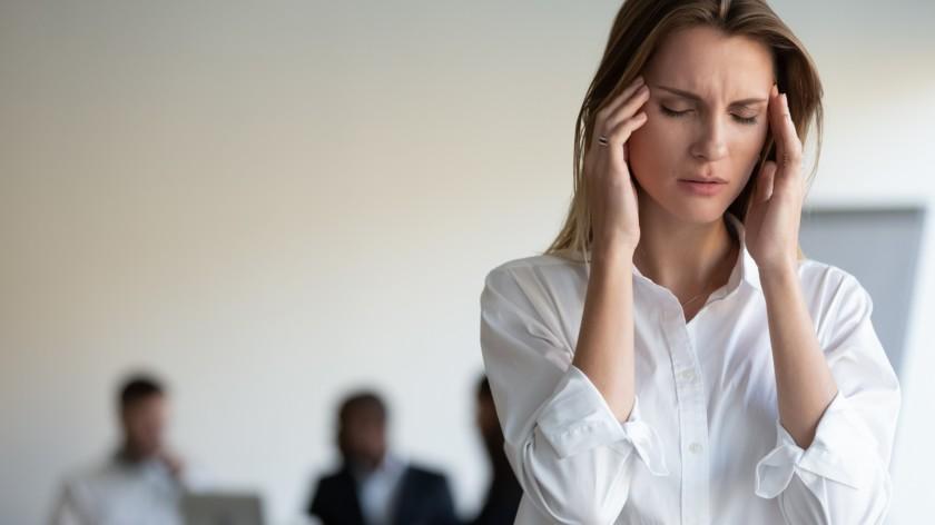 mujer sufren dolor de cabeza debido al estrés en el lugar de trabajo.