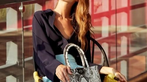 Mujer con ropa de moda sentada en un balcón