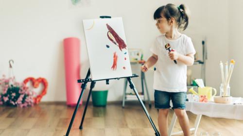 Niña en casa pintando en caballete.