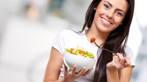 mujer joven comiendo ensalada de verduras y sonriendo