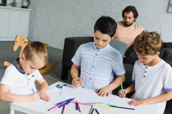 Niños y papá en casa realizando varias actividades como dibujar y leer