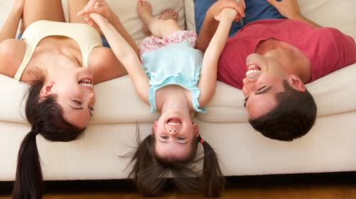 familia acostada en sillón divertida y sonriendo