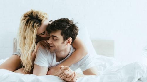 Pareja joven acostados en la cama abrazados de manera muy cariñosa