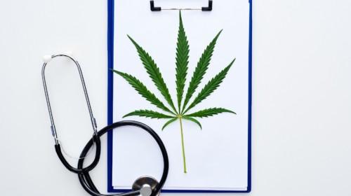 Hoja de cannabis medicinal en el portapapeles cerca del estetoscopio sobre fondo blanco
