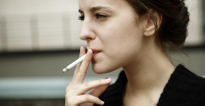 mujer joven fumando un cigarro