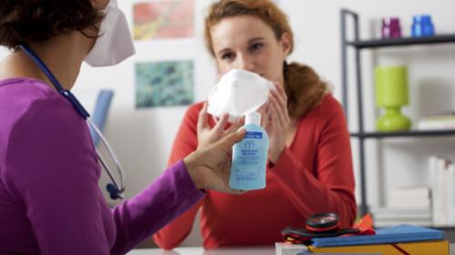 mujer con tapabocas usando gel antibacterial